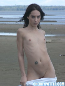 Tiny babe on the beach getting naked